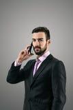 Dramatisk stående för hög kontrast av den allvarliga säkra affärsmannen på mobiltelefonen fotografering för bildbyråer