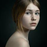 Dramatisk stående av ett flickatema: stående av en härlig flicka på en bakgrund i studion Arkivbilder