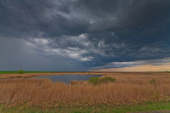 Dramatisk stormhimmel och illavarslande moln över sjön i April royaltyfria bilder