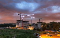 Dramatisk stormig himmel över en konstruktionsplats av en bostads- byggnad med massor av tornkranar Arkivfoton