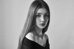Dramatisk svartvit stående av en härlig ensam flicka med fräknar som isoleras på en vit bakgrund i studioskott arkivfoton