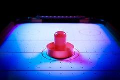 Dramatisk tänd lufthockeytabell med pucken och skovlar Royaltyfri Foto