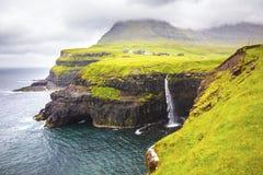 Dramatisk vattenfall på Faroe Island och byn Gasadalur arkivfoton