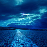 dramatiska moln över asfaltvägen i mörkt månsken Royaltyfri Bild