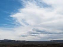 Dramatiska moln över ett berglandskap Arkivbild