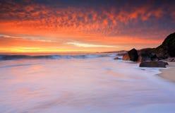 Dramatiska röda himlar och skummiga vitvågor sätter på land Arkivbild