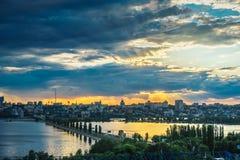 Dramatiska solnedgång- och mörkermoln över den högra banken av Voronezh, Chernavsky bro över vattenbehållare Royaltyfria Bilder