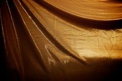 Dramatiskt draperad guld- tygbakgrund Arkivbild