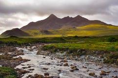 Dramatiskt landskap av Cuillin kullar och floden, skotsk högland Arkivfoto