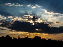 Dramatiskt moln mot solnedgång och stadskontur i botten arkivfoton