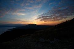 Dramatiskt solnedgånglandskap i höstbergen över moln Härlig skyscape med soliga strålar Arkivfoto