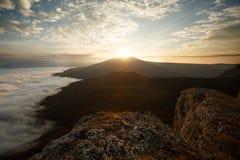 Dramatiskt solnedgånglandskap i höstbergen över moln Härlig skyscape med soliga strålar Arkivbild
