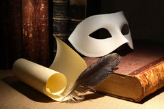 Dramaturgy Concept. Vintage still life with quill and scroll near mask and old books on dark background Stock Image