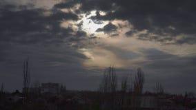 Dramatyczne chmury szybko latają w niebie za domami i drzewami zbiory