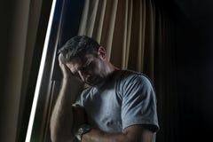 Dramatyczny światła indoors portret młody smutny, przygnębiony atrakcyjny mężczyzna patrzeje przez i i zdjęcie stock