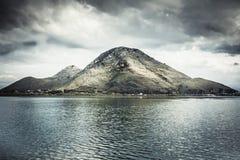 Dramatyczny krajobraz z górą przy linią brzegową wyspa i spokojną wodą z nieba odbiciem w chmurzącym dniu z markotnym niebem Obrazy Stock