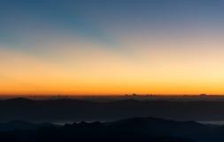 Dramatyczny mroczny zmierzch i wschodu słońca niebo nad górą i mgłą Obraz Stock