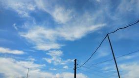 Dramatyczny niebieskie niebo z elektrycznym drutem i poczta Fotografia Stock
