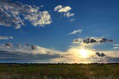 Dramatyczny zmierzch nad polami z chmurami podczas późnego lata obrazy stock