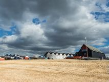 Dramtic sky over Whitstable beach, Kent, UK. Dramatic cloudscape over the beach in Whitstable, looking from the sand up towards the black wooden fishermen`s huts Stock Photography