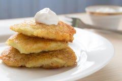 Draniki - buñuelos de la patata Crepes de patata Plato nacional de Bielorrusia, de Ucrania y de Rusia con crema agria imagen de archivo