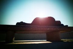 Drank adult man rests on stony  bench in park, Sharp sun rays Royalty Free Stock Photos