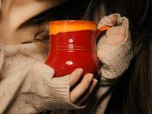 drank De rode kopmok van heet drinkt theekoffie in handen Stock Foto's