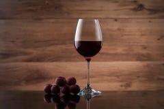 Drank en voedsel Wijnglas, met rode wijn en rode druiven stock fotografie