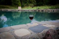 Drank in lang glas in poolside Verfrissing op de zomerdag Purpere sapcocktail of wijnstok Berg bosachtergrond royalty-vrije stock foto
