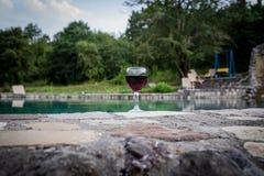 Drank in lang glas in poolside Verfrissing op de zomerdag Purpere sapcocktail of wijnstok Berg bosachtergrond royalty-vrije stock foto's