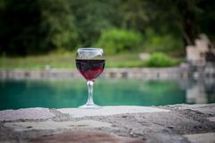 Drank in lang glas in poolside Verfrissing op de zomerdag Purpere sapcocktail of wijnstok Berg bosachtergrond stock fotografie