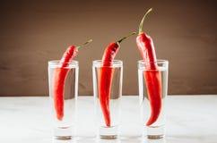 Drank met drie die schoten van wodka en Spaanse peper wordt/Drank met drie schoten van wodka en Spaanse peper wordt geplaatst gep royalty-vrije stock foto