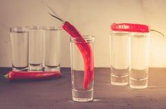 Drank met schoten van wodka en Spaanse peper wordt/Drank met schoten van wodka en Spaanse peper wordt geplaatst geplaatst die Sel stock foto