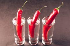 Drank met schoten van wodka en Spaanse peper/Drank wordt geplaatst met schoten van wodka wordt geplaatst en Spaanse peper op een  stock afbeeldingen