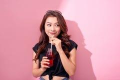 Dranken, mensen en levensstijlconcept - sluit omhoog van gelukkige vrouw het drinken kola met stro thuis stock fotografie