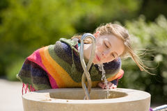 Dranken van het blonde de jonge meisje bij openbare fontein Royalty-vrije Stock Afbeelding