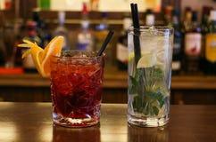 Drankenconcept Koude transparante cocktails met ijsblokjes De achtergrond van onduidelijk beeldflessen, sluit omhoog mening stock afbeeldingen