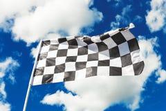 Drapeau à carreaux ondulant avec le ciel bleu et les nuages derrière lui Image filtrée : effet de vintage traité par croix image libre de droits