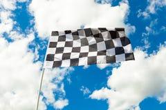 Drapeau à carreaux sur le mât de drapeau ondulant dans le vent images libres de droits