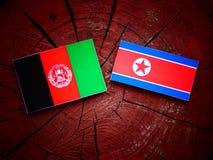 Drapeau afghani avec le drapeau coréen du nord sur un tronçon d'arbre Photo libre de droits