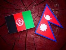 Drapeau afghani avec le drapeau de Nepali sur un tronçon d'arbre d'isolement Photo libre de droits