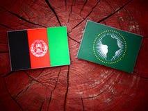 Drapeau afghani avec le drapeau des syndicats africains sur un tronçon d'arbre Photographie stock