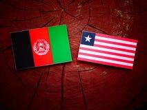 Drapeau afghani avec le drapeau libérien sur un tronçon d'arbre d'isolement Photographie stock libre de droits