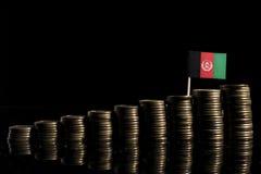 Drapeau afghani avec le sort de pièces de monnaie d'isolement sur le noir Photographie stock
