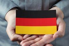 Drapeau allemand dans des paumes Image libre de droits