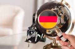 Drapeau allemand sur le globe par l'agrandissement photographie stock libre de droits