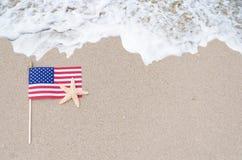 Drapeau américain avec des étoiles de mer sur la plage sablonneuse Photo stock