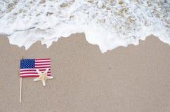 Drapeau américain avec des étoiles de mer sur la plage sablonneuse Photographie stock libre de droits