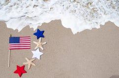 Drapeau américain avec des étoiles de mer sur la plage sablonneuse Photographie stock