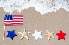 Drapeau américain avec des étoiles de mer sur la plage sablonneuse Images libres de droits